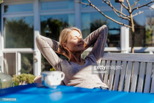 Woman relaxing on garden bench