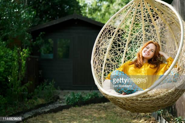 woman relaxing on garden swing seat - endast en ung kvinna bildbanksfoton och bilder