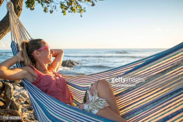 frau entspannen auf hängematte bei sonnenuntergang am strand - pazifikinseln stock-fotos und bilder