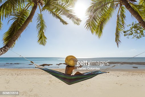 Woman Relaxing On Hammock Under Palm Tree On A Tropical