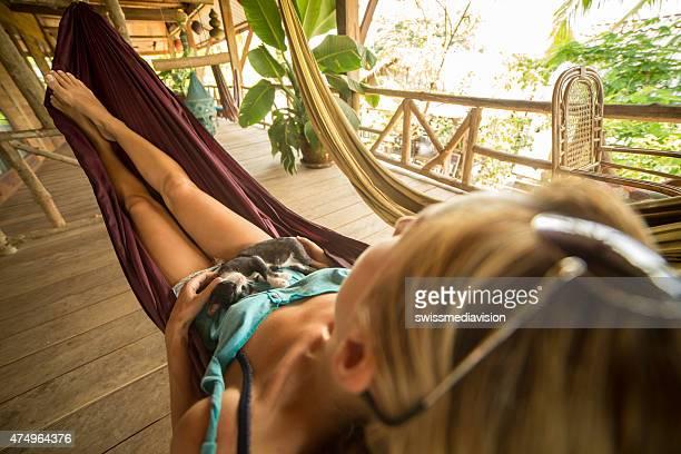 Frau Entspannen auf der Hängematte mit Ihrem Kätzchen