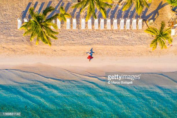 woman relaxing on idyllic beach - idílico fotografías e imágenes de stock