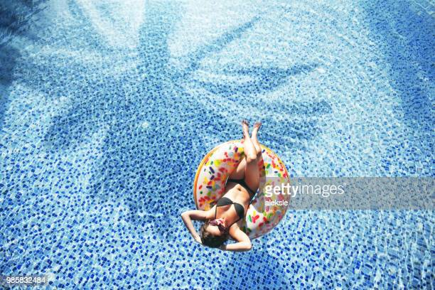 Woman relaxing on inflatable ring donut in the pool