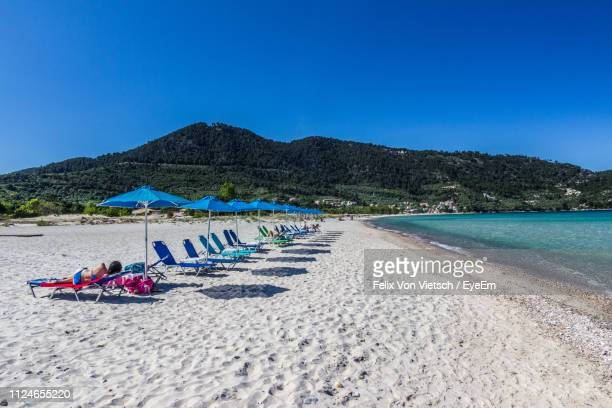 woman relaxing on lounge chair at beach against sky - thasos stock photos and pictures