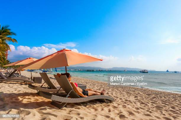 Woman Relaxing On Lounge Chair At Beach Against Sky