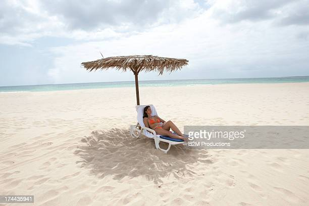 woman relaxing on lounge chair at beach - cabo verde imagens e fotografias de stock