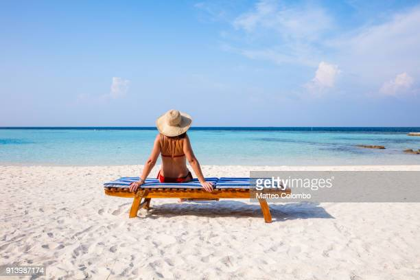 woman relaxing on lounge chair on the beach, maldives - femme plage photos et images de collection