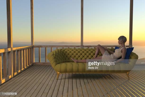 woman relaxing on luxury sofa, on summer evening - una sola mujer joven fotografías e imágenes de stock
