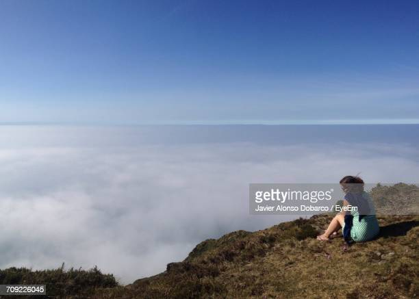 woman relaxing on mountain by clouds against blue sky - javier alonso fotografías e imágenes de stock