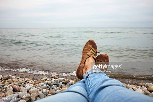 Woman relaxing on pebble beach, low section