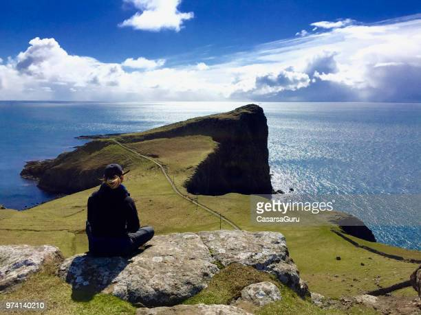 woman relaxing on scottish coastline - national landmark stock pictures, royalty-free photos & images