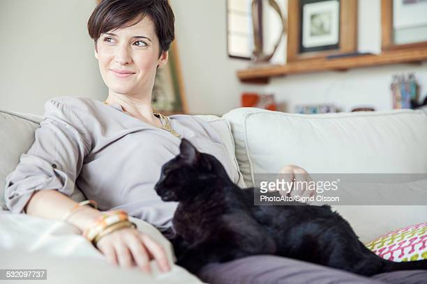 Woman relaxing on sofa with cat on her lap