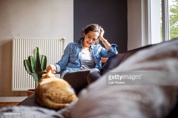 woman relaxing on sofa with her cat - one animal stock pictures, royalty-free photos & images
