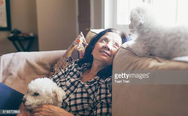 Woman relaxing on sofa with two dogs
