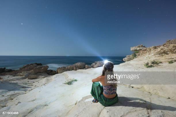 Frau, entspannend am einsamen Strand in der Nacht