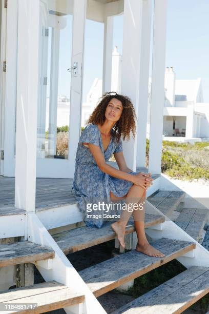 woman relaxing on steps in front of beach house - holiday villa stock pictures, royalty-free photos & images