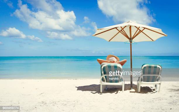 woman relaxing on sunbed on the beach - mauritius stock photos and pictures