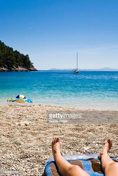 Woman relaxing on the beach, Korcula island, Dubrovnik Neretva, Dalmatia, Croatia, Europe