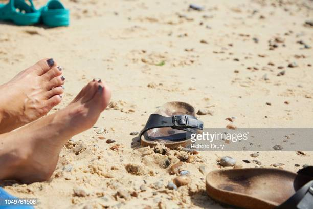 Woman relaxing on the beach with her sandals kicked off