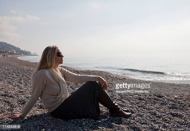 Woman relaxing on uncrowded pebble beach