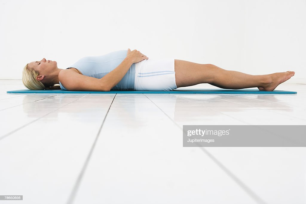 Woman relaxing on yoga mat : Stock Photo