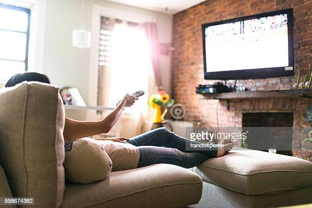 woman relaxing online on sofa reading some papers - kanaal stockfoto's en -beelden