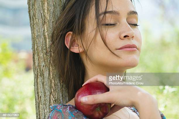 Woman relaxing outdoors with eyes closed, holding apple