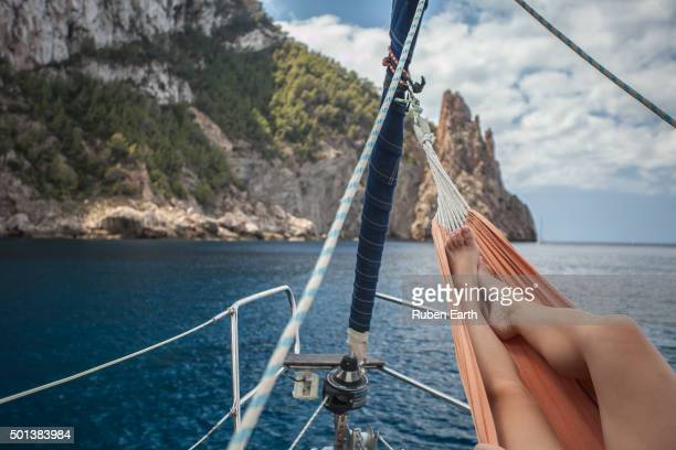 A woman relaxing over a hammock attached to a sailing boat mast in Ibiza island shore