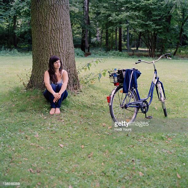 a woman relaxing under a tree next to a bicycle - alleen één mid volwassen vrouw stockfoto's en -beelden