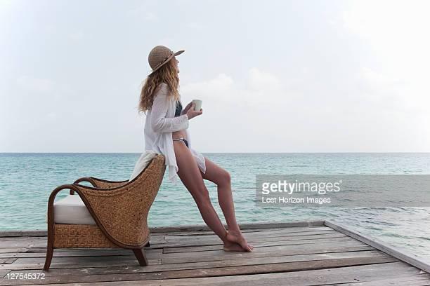 女性、デッキでリラックスしたコーヒー