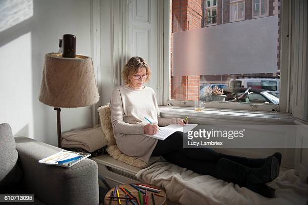 woman relaxing with coloring book - colouring book stock pictures, royalty-free photos & images