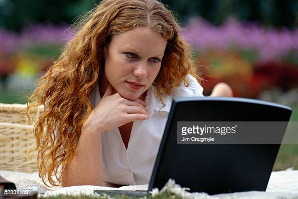 woman relaxing with laptop at park - jim craigmyle stock pictures, royalty-free photos & images
