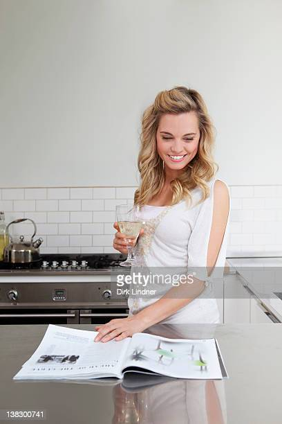woman relaxing with wine and magazine - glass magazine stock photos and pictures
