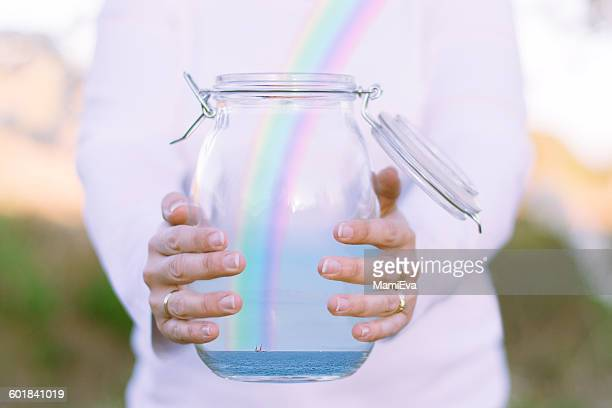 Woman releasing a rainbow over ocean from a glass jar