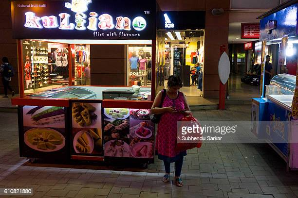 A woman remains busy with her mobile phone in front of an icecream parlor at a big shopping mall