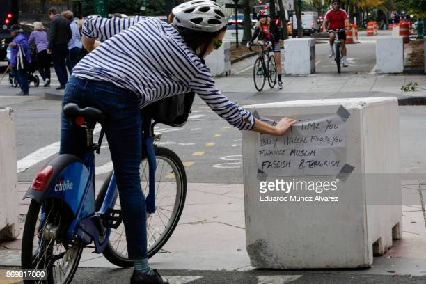 A woman removes a note placed of a barricade next to the scene of Tuesday's terrorist attack along a bike path in lower Manhattan on November 3 2017...