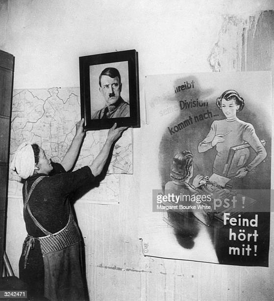 A woman removes a portrait of Hitler from the wall of a protestant church in Frankfurt which had been used by the Nazis as a party headquarters On...