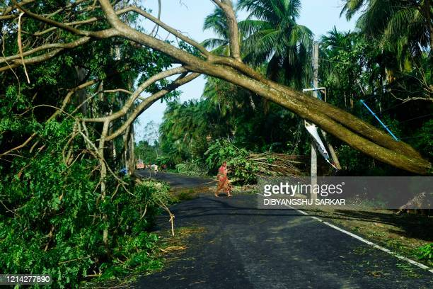 TOPSHOT A woman removes debris from a road after the landfall of cyclone Amphan in Midnapore West Bengal on May 21 2020 The strongest cyclone in...