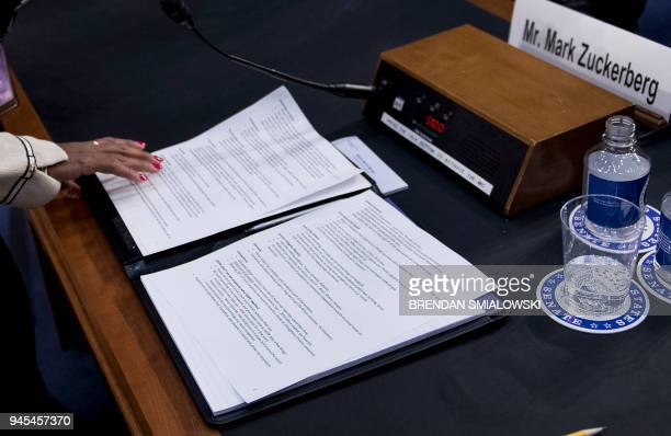 A woman removes Facebook CEO Mark Zuckerberg's notes from a talk during a joint hearing of the Senate Commerce Science and Transportation Committee...