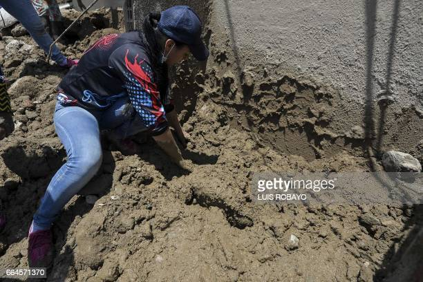 A woman removes stones looking for her missing relatives after mudslides caused by heavy rains in Mocoa Putumayo department southern Colombia on...