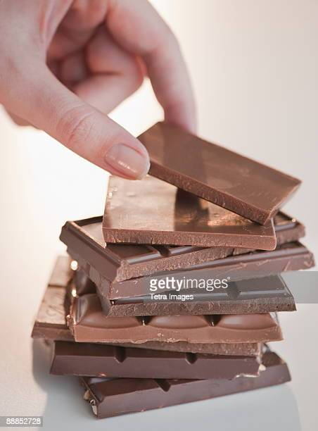 woman removing bar of chocolate from stack, close-up - chocolate bar stock pictures, royalty-free photos & images