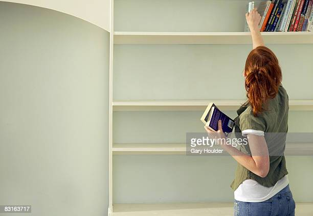 woman removing books from the shelf - neat stock pictures, royalty-free photos & images