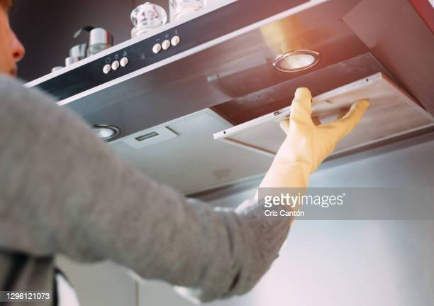 woman removing dirty filter from kitchen fan - cris cantón photography fotografías e imágenes de stock
