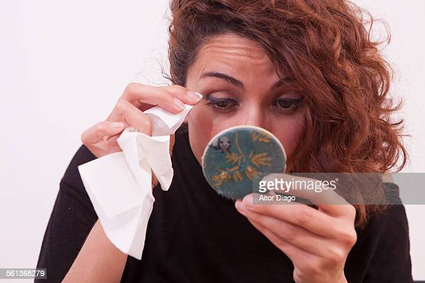 Woman removing eye makeup in mirror with a tissue