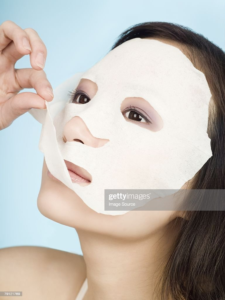 Woman removing face mask : Stock Photo
