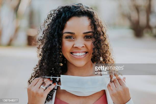 woman removing face protection mask and smiling - removal stock pictures, royalty-free photos & images