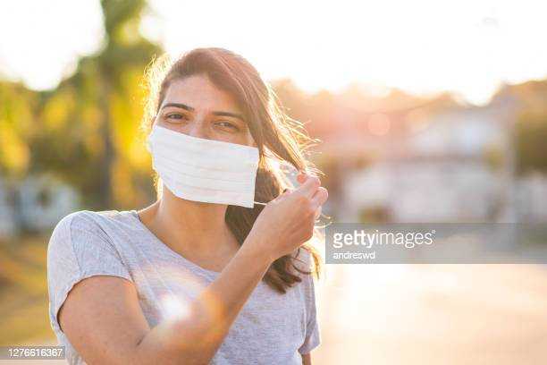 woman removing face protection mask - absence stock pictures, royalty-free photos & images
