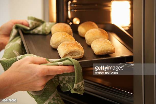 Woman removing fresh baked breadcakes from an oven