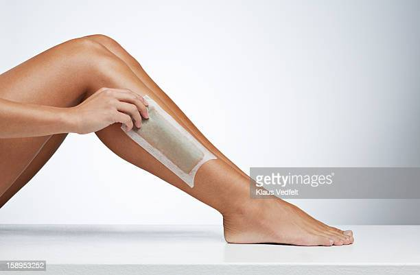 Woman removing hair on the leg with wax strip
