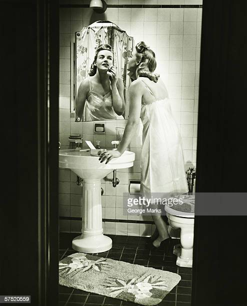 Woman removing make up in front of mirror in bathroom, (B&W)